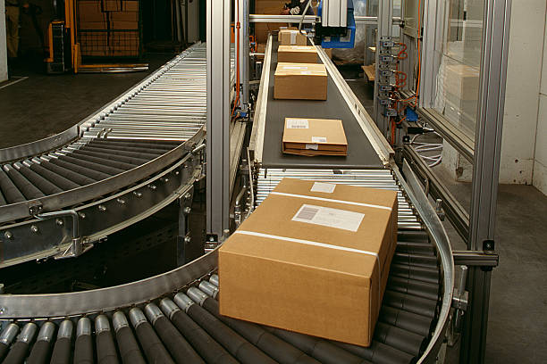 conveyor belt curve showing brown packed postal boxes - conveyor belt stock pictures, royalty-free photos & images