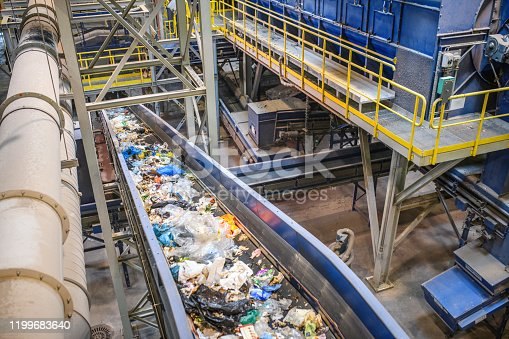 High angle close-up of pieces of recyclable garbage on conveyor belt inside waste management facility.