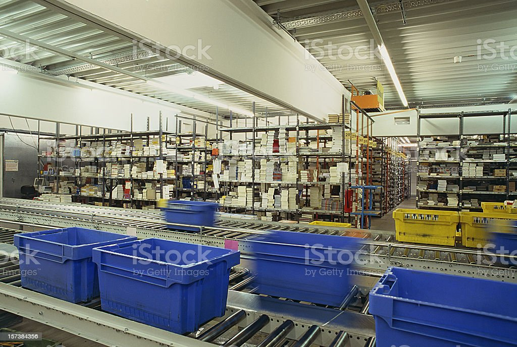 Conveyor belt warehouse storage distribution with blue plastic boxes stock photo
