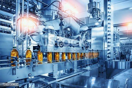 Conveyor belt with juice bottles on beverage factory interior in blue color.