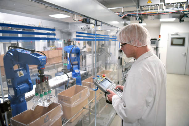 conveyor belt worker operates a robot that transports insulin bags - modern factory for the production of medicines in the healthcare sector - robotics manufacturing stock photos and pictures