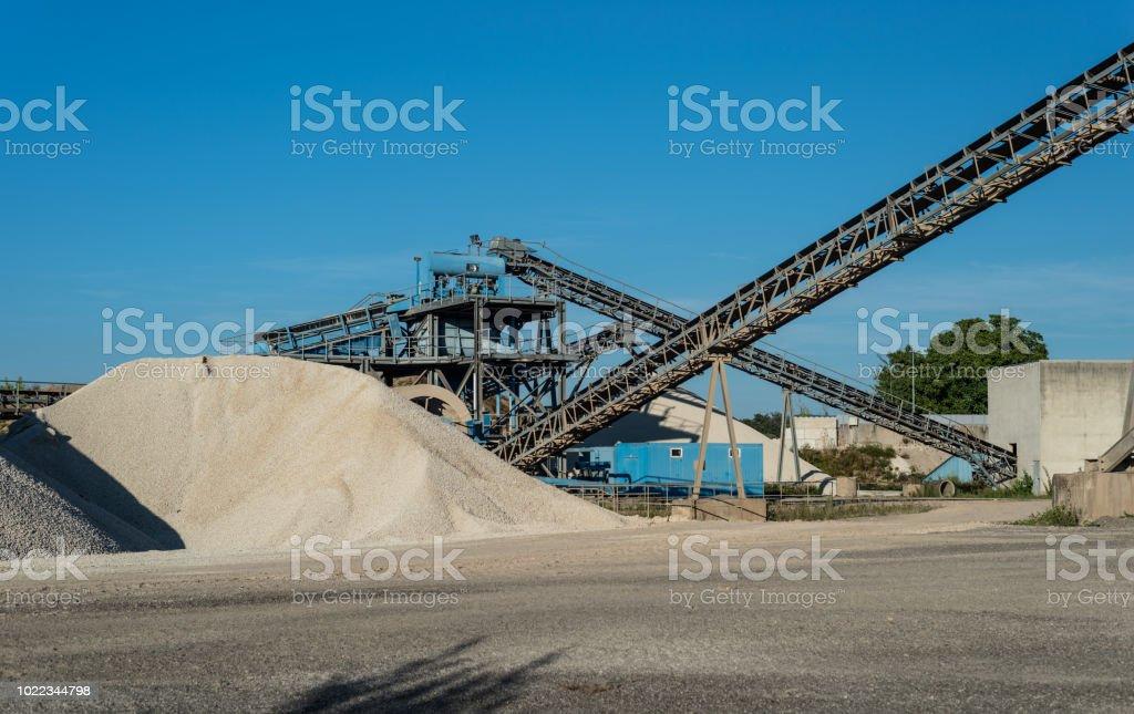 Förderband über haufenweise Kies auf blauen Himmel bei einem industriellen Zementwerk. – Foto