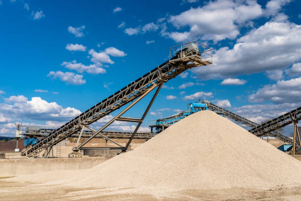 Fördermittel über Schotterhaufen auf blauem Himmel in einem industriellen Zementwerk. – Foto