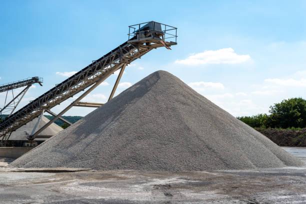 förderband über haufenweise kies auf blauen himmel bei einem industriellen zementwerk. - betonwerkstein stock-fotos und bilder