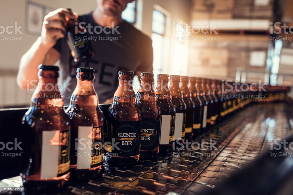 Conveyor with beer bottles moving in brewery factory stock photo