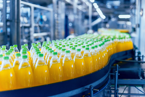 Conveyor with bottles for juice or water. Beverages factory equipments. Background