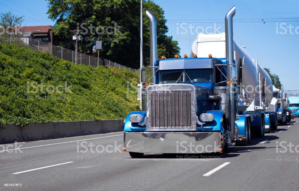 Convoy of big rigs semi trucks on the road with blue classic American bonnet semi tractor with bulk trailer stock photo