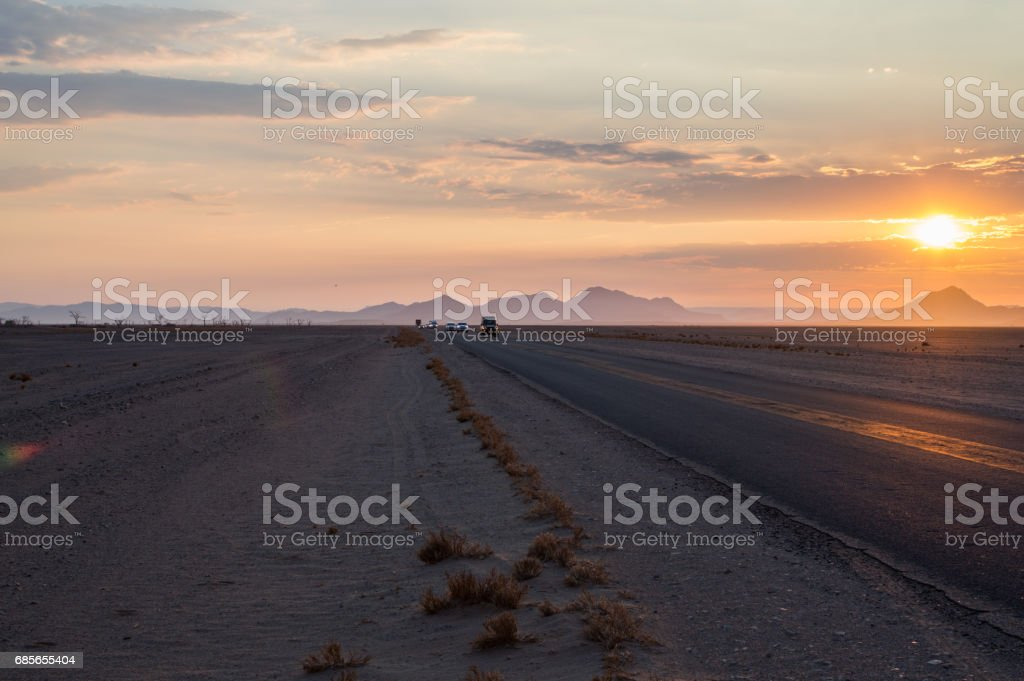 Convoy of Cars Driving on a Highway in the Desert at Sunrise, Sossusvlei, Namibia royalty-free stock photo