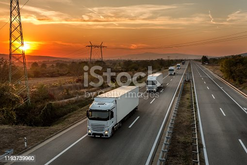 Convoy of blue lorry trucks on a country highway under amazing orange sunset sky. Highway transportation with white lorry tracks in caravan or convoy