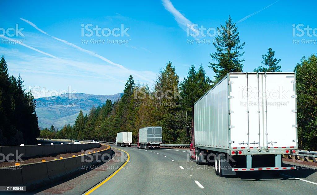 Convoy Semi trucks dry van trailers winding highway stock photo