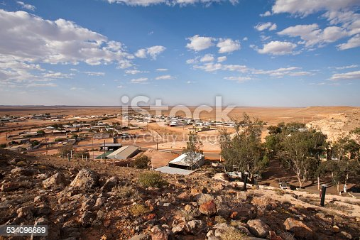 An evening landscape photo of Coober Pedy, South Australia, including houses, trees, the surrounding desert and rocks in the foreground. Photo taken from a hill lookout