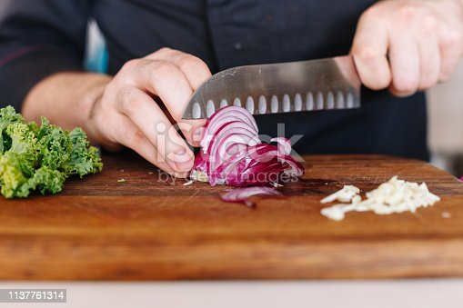 Cook cuts onion and garlic