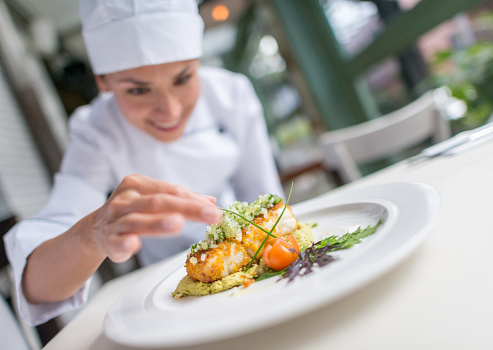 Woman cook decorating a beautiful plate at an elegant restaurant