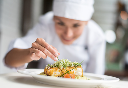 Cook decorating a plate and putting the ultimate touches - focus on foreground