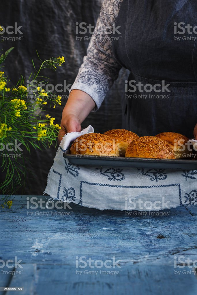 Cook holds in a hand buns for hamburgers stock photo