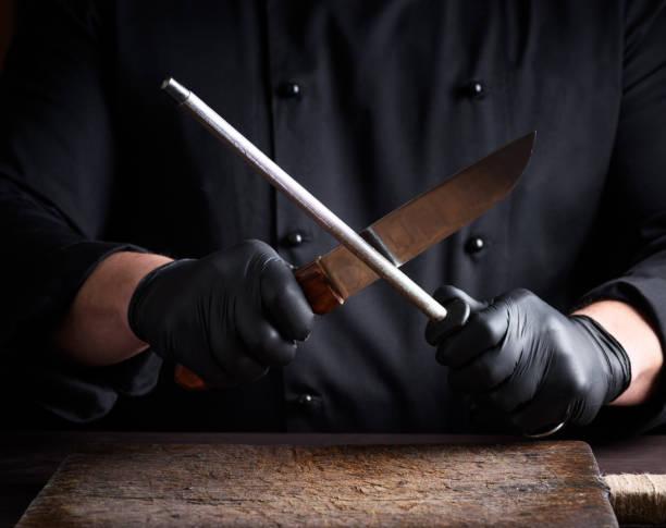 cook zwarte latex handschoenen scherpt een mes - keukenmes stockfoto's en -beelden