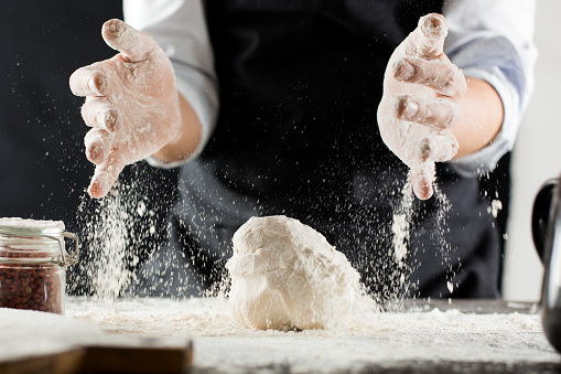istock Cook kneads dough with flour on kitchen table 1132995099