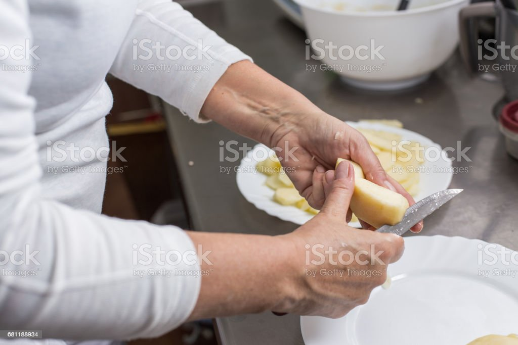 cook peeling apples in the kitchen royalty-free stock photo