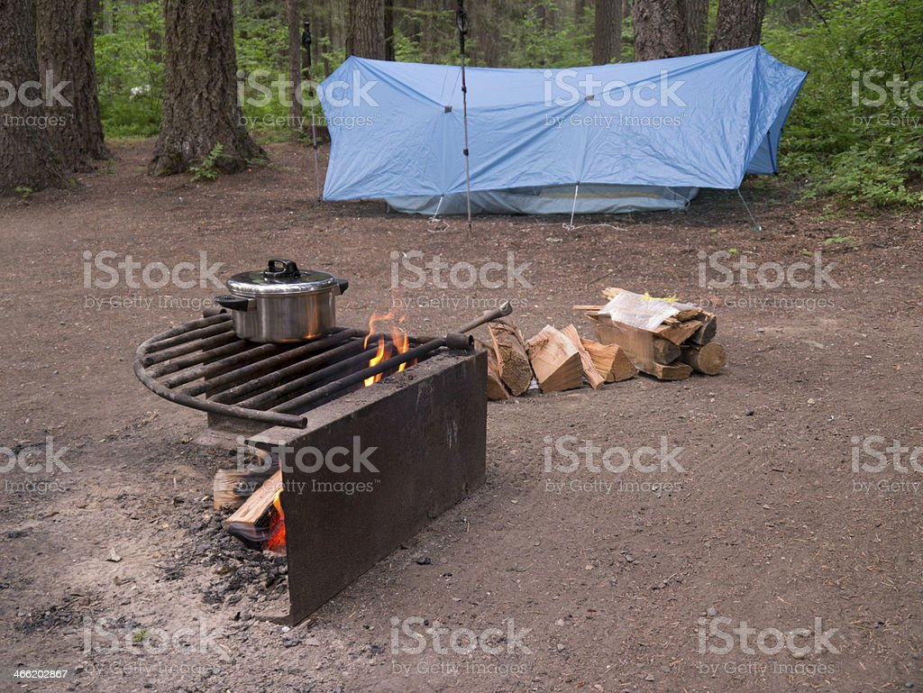 Cook pot over campfire, tarp tent in background