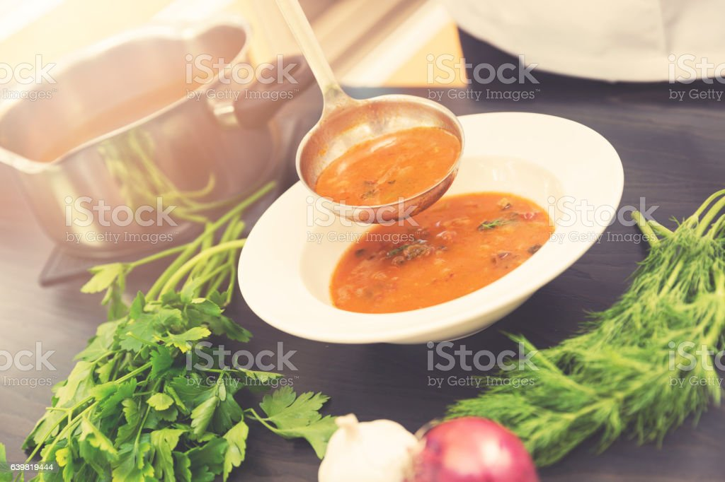 cook pouring soup with ladle into a plate stock photo