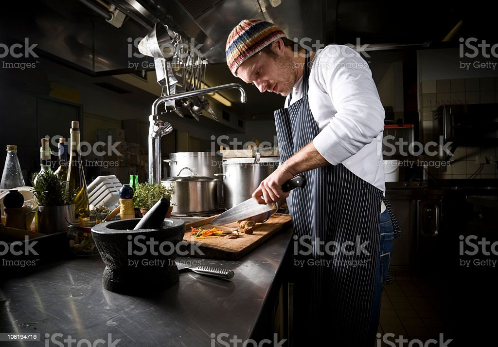 A cook preparing a meal in the dark stock photo