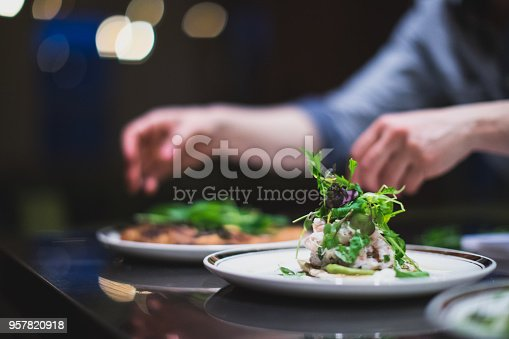 Cook preparing many plates in a restaurant kitchen. Caterer in Canada