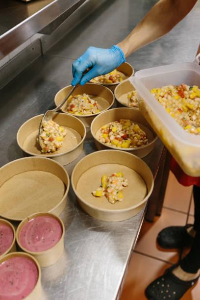 Cook preparing takeaway salads stock photo