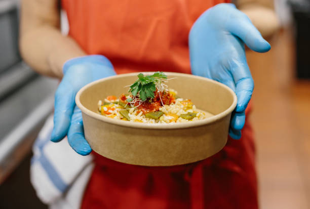 A cook presents her gourmet rice salad in a compostable take-away container stock photo
