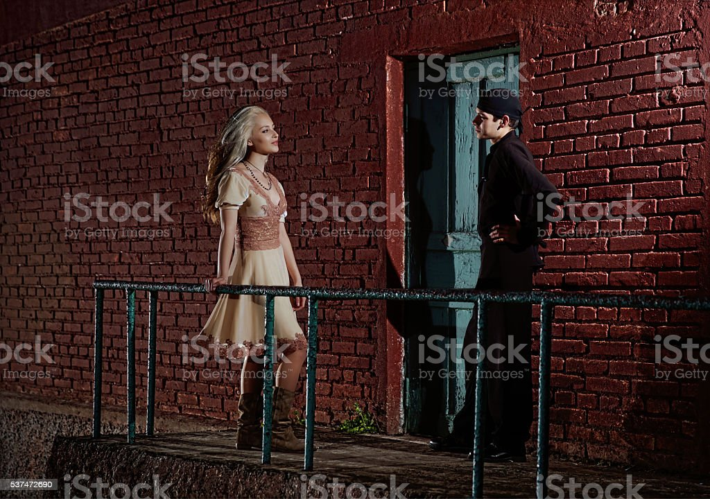Cook standing near kitchen backdoor talking with a girl stock photo