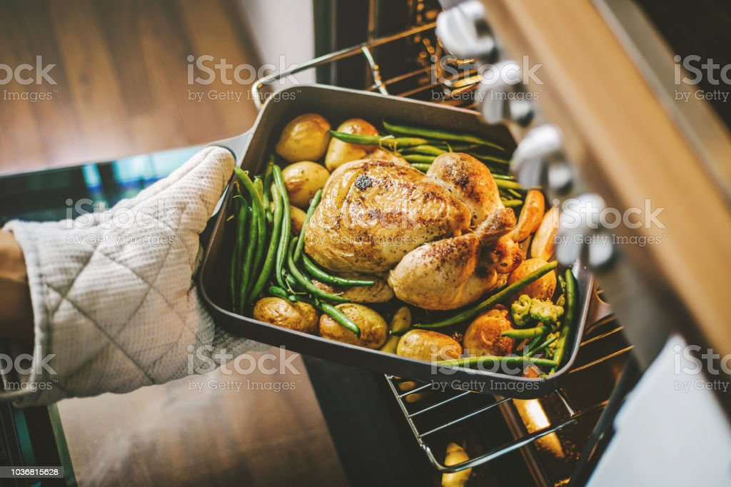Cook taking ready chicken from the oven stock photo