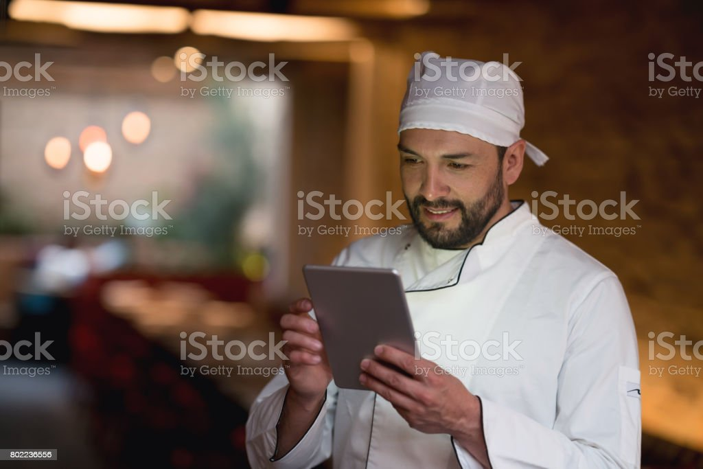 Cook using a tablet computer at a restaurant stock photo