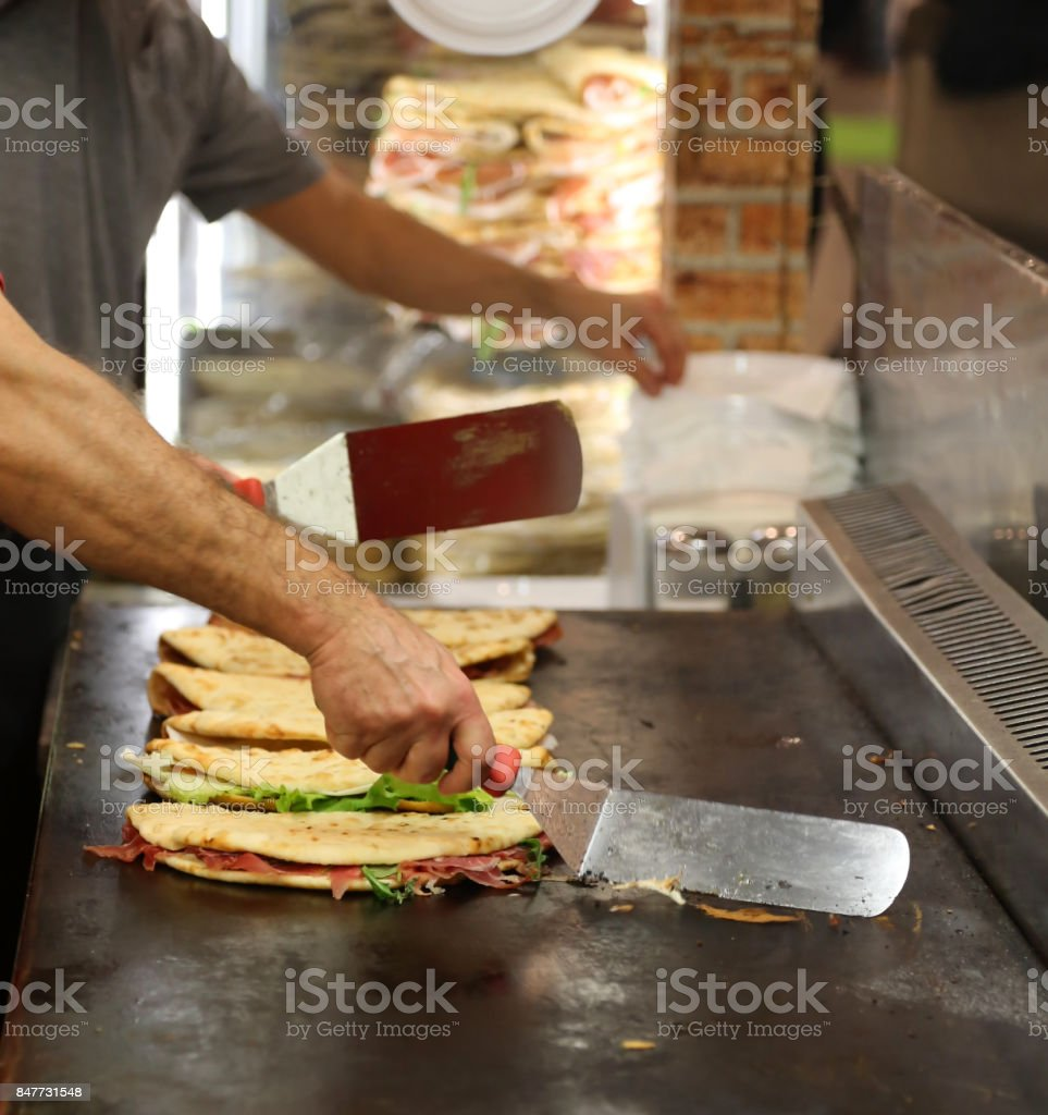 cook while cooking the piadina in the roaring grill of the outdo stock photo