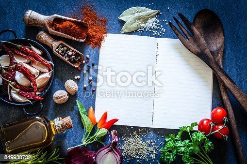 istock Cookbook with spices and herbs on dark kitchen table 849938732