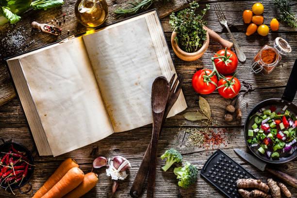 livro de receitas com legumes, especiarias e ervas atirou por cima, na mesa de madeira rústica - receita - fotografias e filmes do acervo