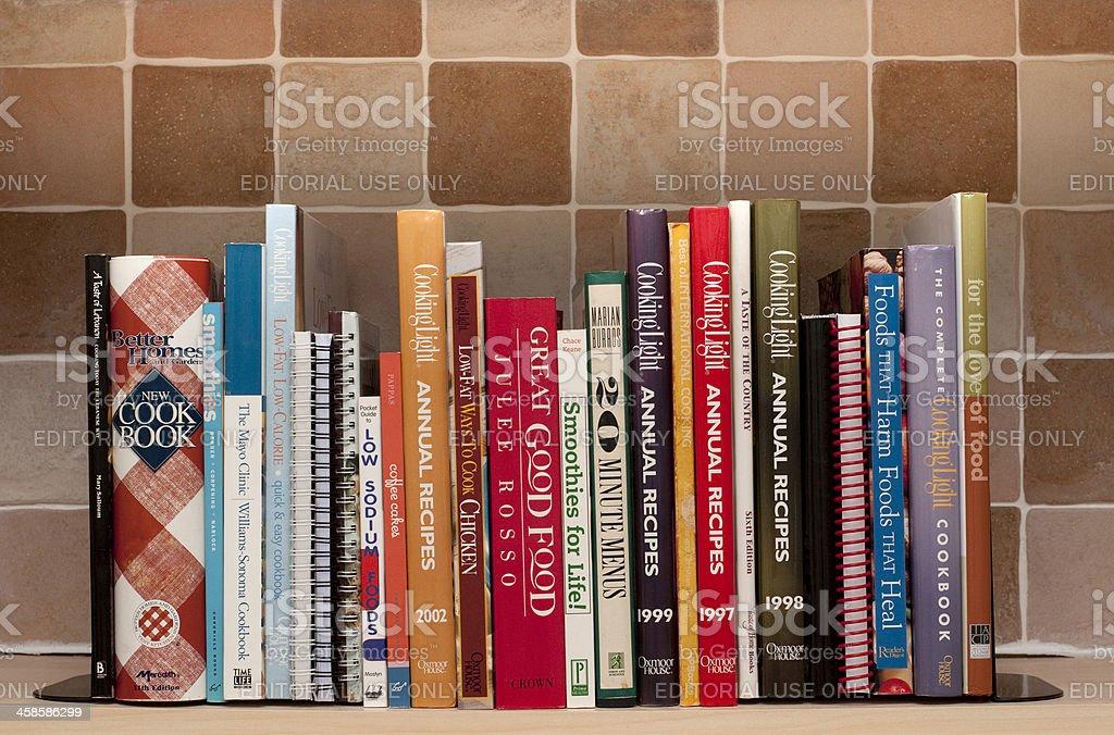 Cookbooks on kitchen shelf stock photo