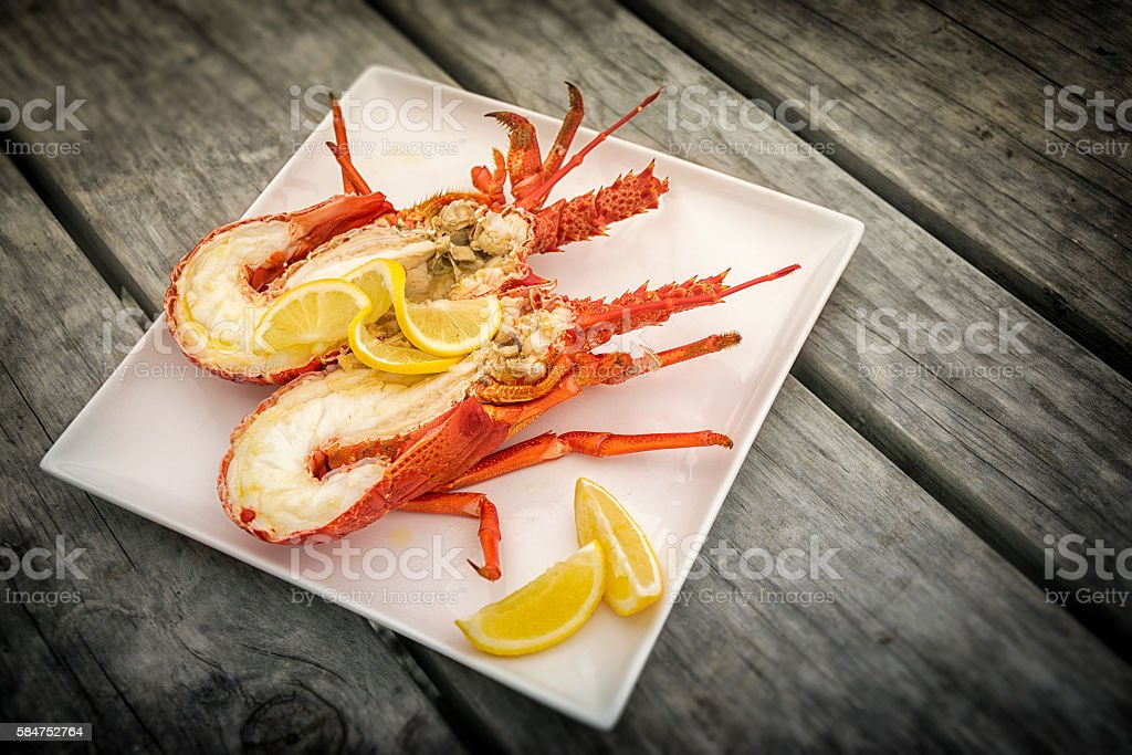 Cooked and halved New zealand crayfish on the wooden table. stock photo