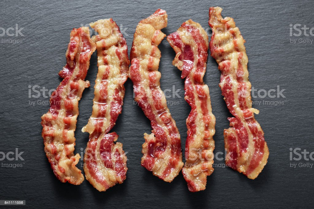Cooked bacon rashers on the background of a slate board stock photo