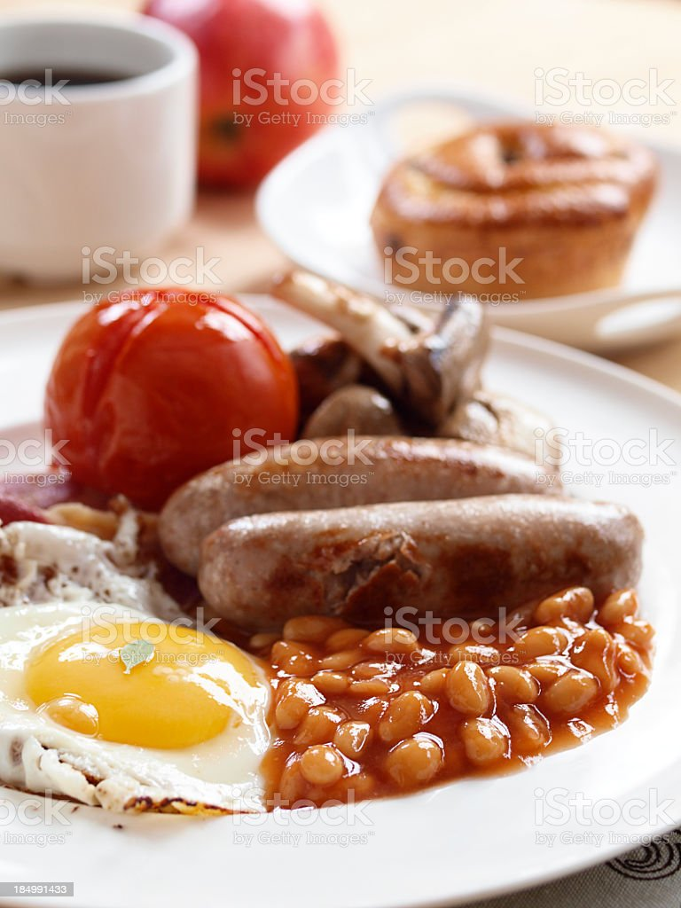 Cooked breakfast of fried egg baked beans sausage and tomato stock photo
