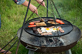 Woman tending to a cooked English breakfast breakfast over a fire pit.