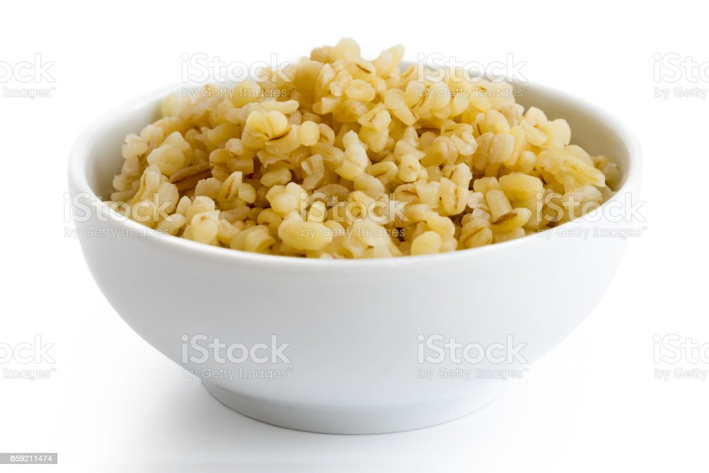 Cooked bulgur wheat in white ceramic bowl isolated on white. - Photo