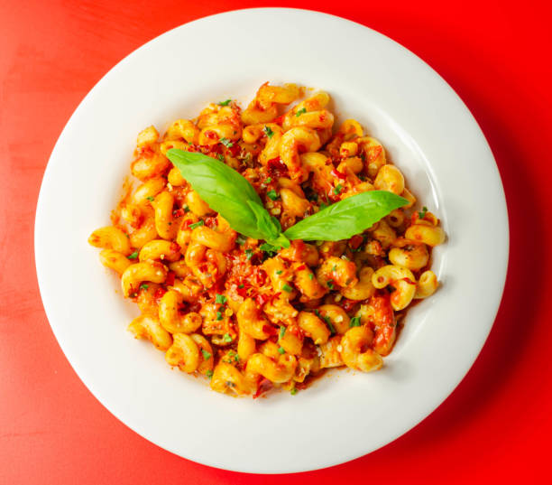 Macarrão de cellentani cozido com peito de frango cozido e pimentas em um molho de tomate picante - foto de acervo