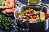 cooked chicken stock with vegetables and aromatic herbs in a stockpot and in a mug at the background, ingredients on a stone kitchen worktop, horizontal view, close-up