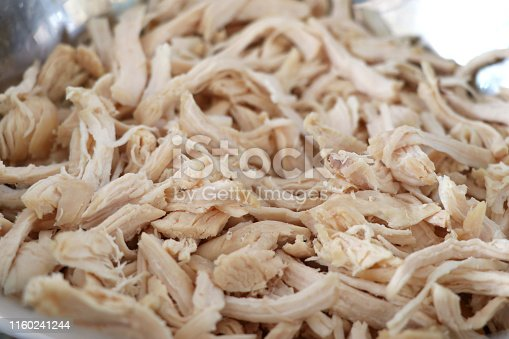 Cooked chicken that is shredded in a container. Shredded chicken in the cup.