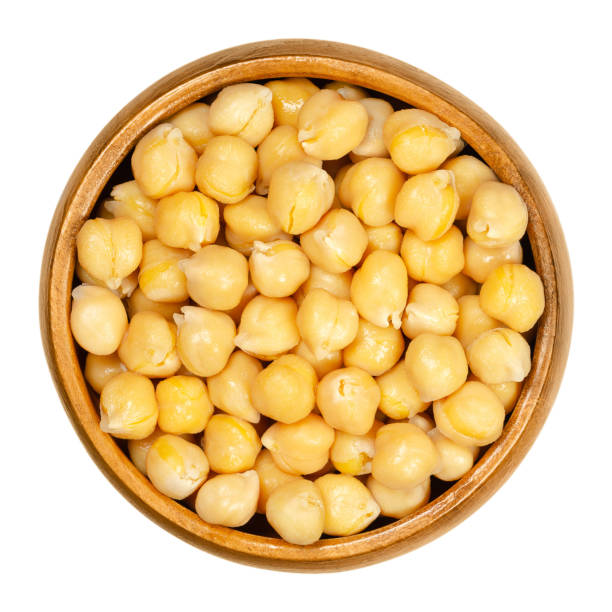Cooked chickpeas in wooden bowl over white Cooked chickpeas in wooden bowl. Light tan Kabuli chickpea variety. Chick peas, Cicer arietinum, high protein legume and ingredient of hummus. Closeup from above on white background, macro food photo. chick pea stock pictures, royalty-free photos & images