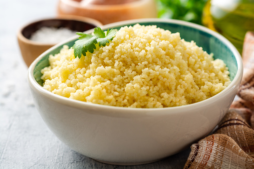 Cooked Couscous With Cilantro In Ceramic Bowl On Concrete Background Stock Photo - Download Image Now