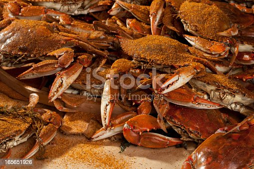 A pile of cooked blue crabs covered in Old Bay spices and ready to be eaten.