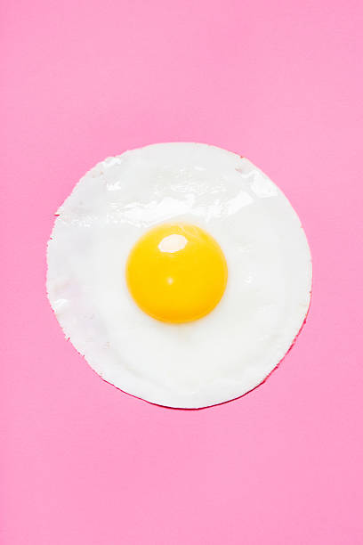 cooked egg on pink - fried egg stock photos and pictures