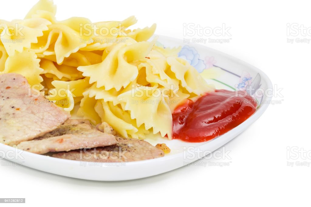 Cooked farfalle pasta with fried pork and ketchup closeup stock photo