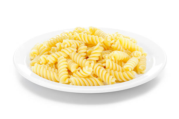 Cooked fusilli pasta Cooked fusilli pasta in a white plate isolated on white. More fusilli... fusilli stock pictures, royalty-free photos & images