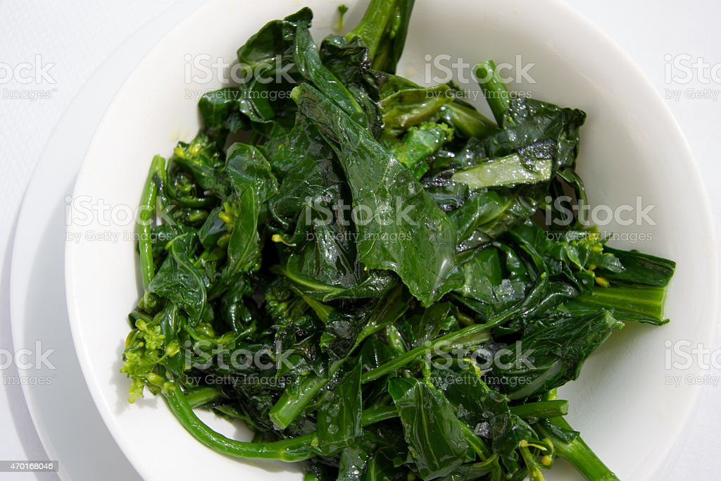 Cooked Greens on White Dishes and White Tablecloth stock photo
